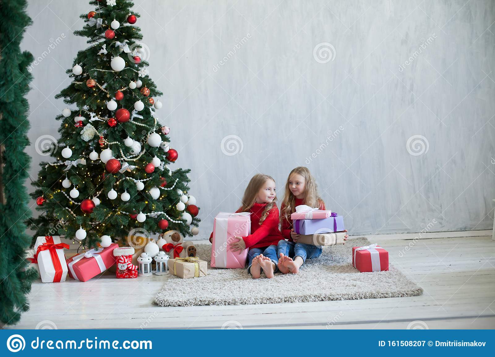 Two Girl Sisters Open Christmas Gifts At The Tree New Year ...
