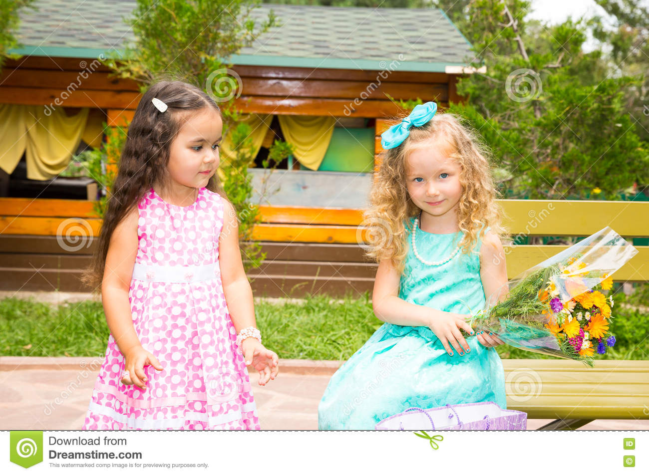 Two girlfriends. Adorable little children with bouquet of flowers on happy birthday. Kid in park