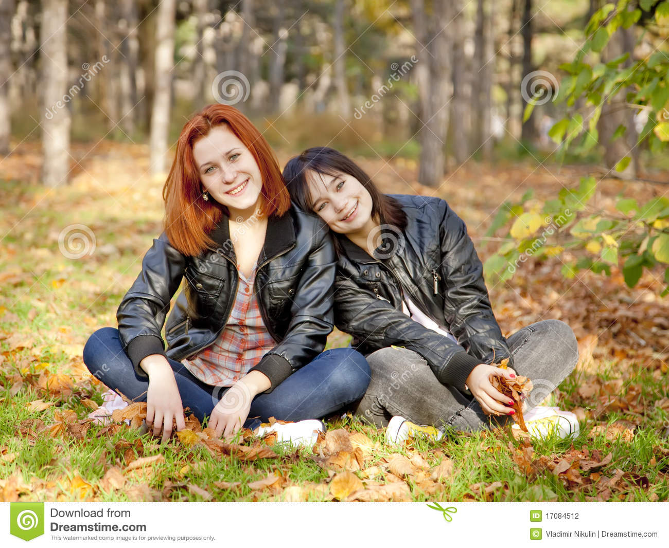 Two girlfriends at the autumn park.