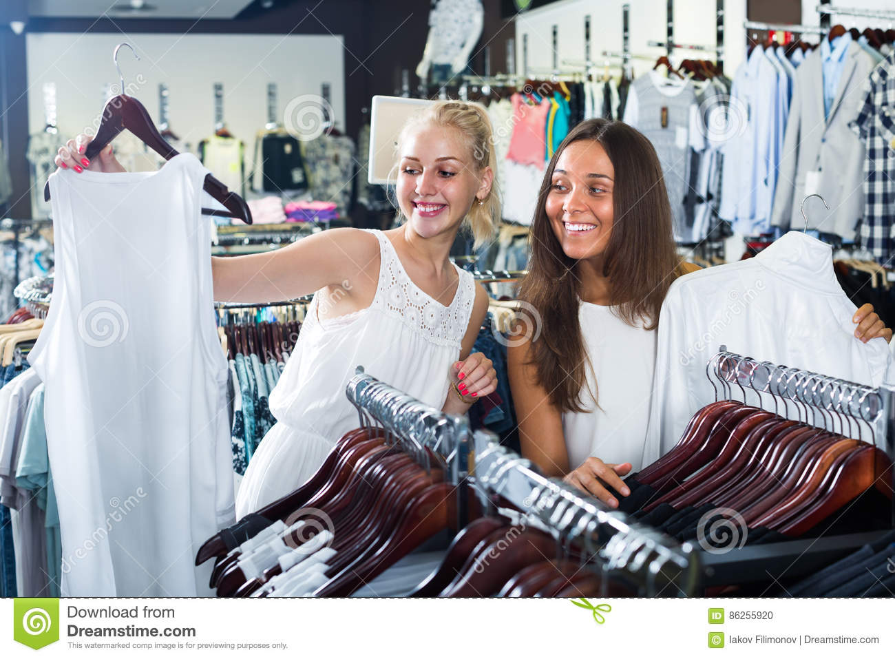 a2097c4ab8 Two cheerful smiling young girls shopping new shirt together in clothes  store. More similar stock images
