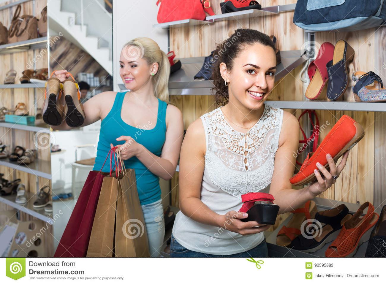 Two Girls Choosing Shoes In The Store