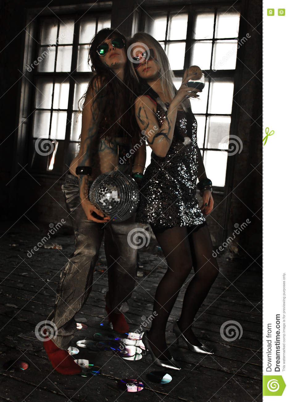 Two girls dancing with disco ball at abandoned house