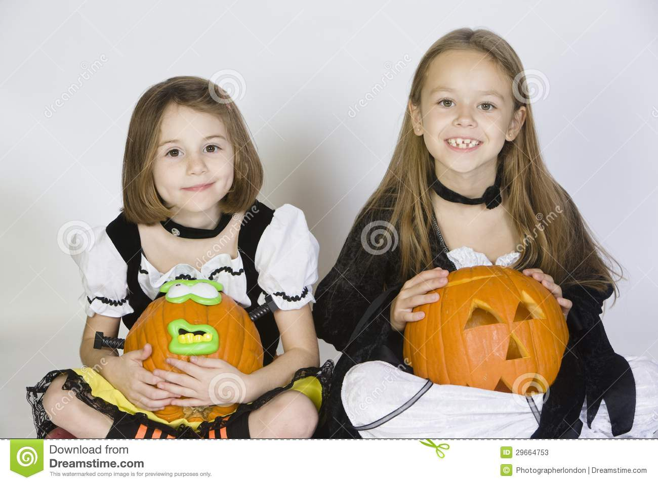 download two girls dressed in halloween costumes holding jack o lanterns stock image