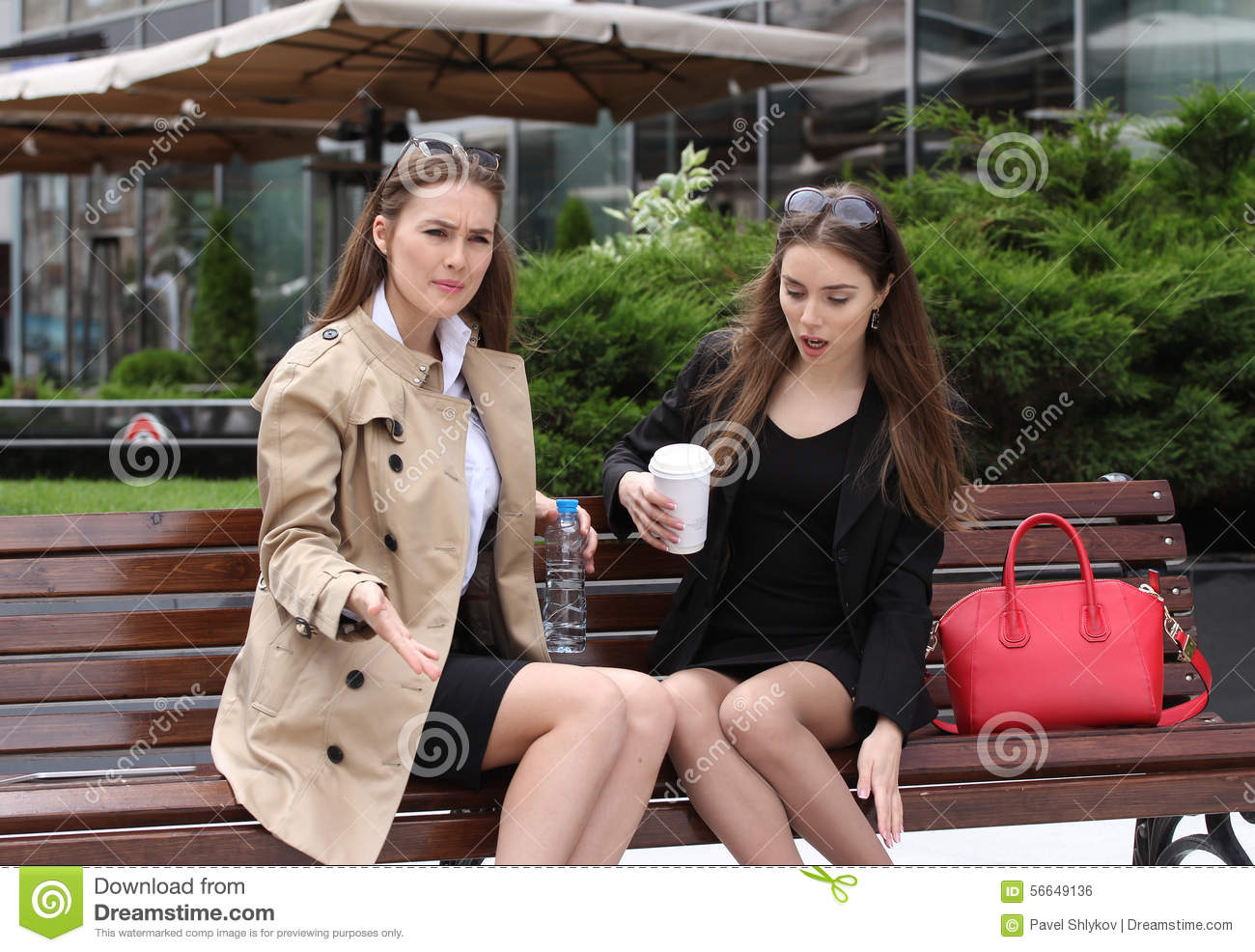 Two Girls Drinking Coffe On A Park Bench Stock Photo
