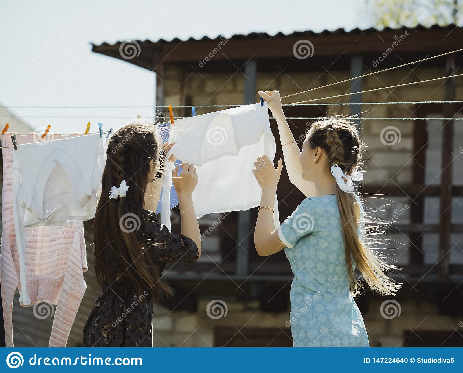 two girls dry clothes on the street.