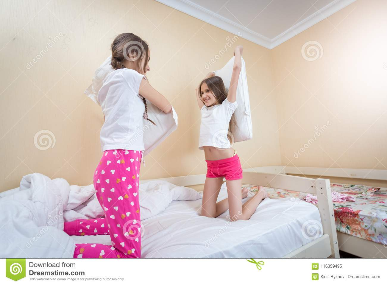 Two Beautiful Girls Fighting With Pillows On Bed At Bedroom ...