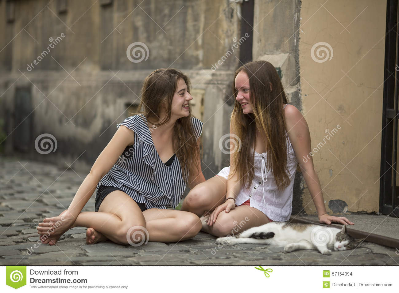 Two girls girlfriend with a cat sitting on the pavement on the street.