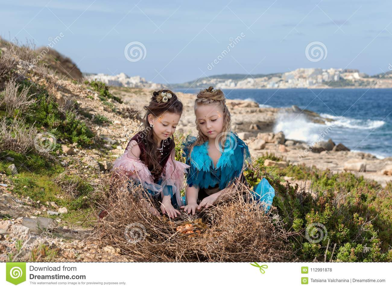 Two girls with hair nests and bird dresses looking at eggs in a large nest