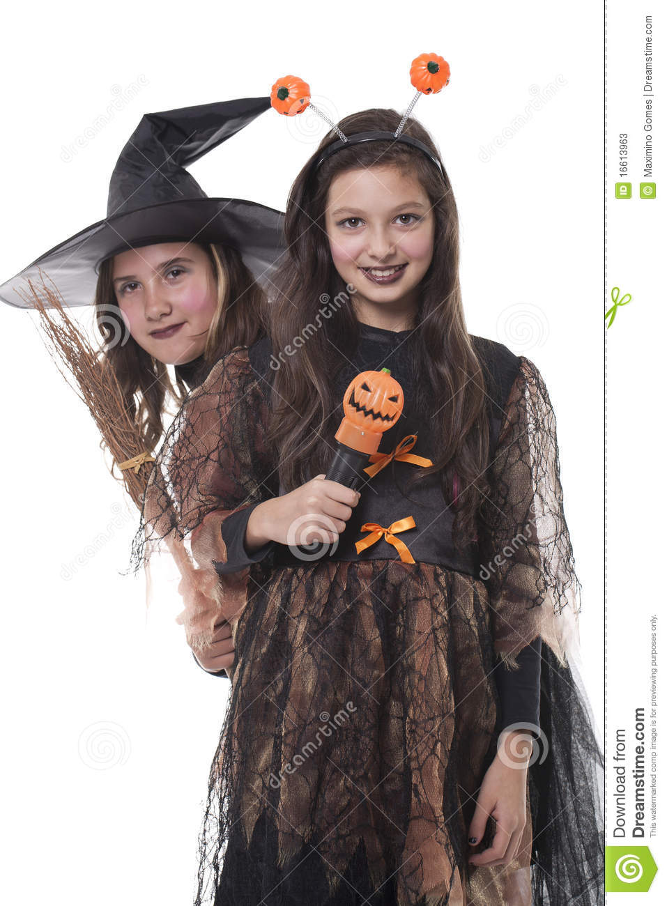 Photo of two girls in halloween costume, broom and pumpkin and having ...