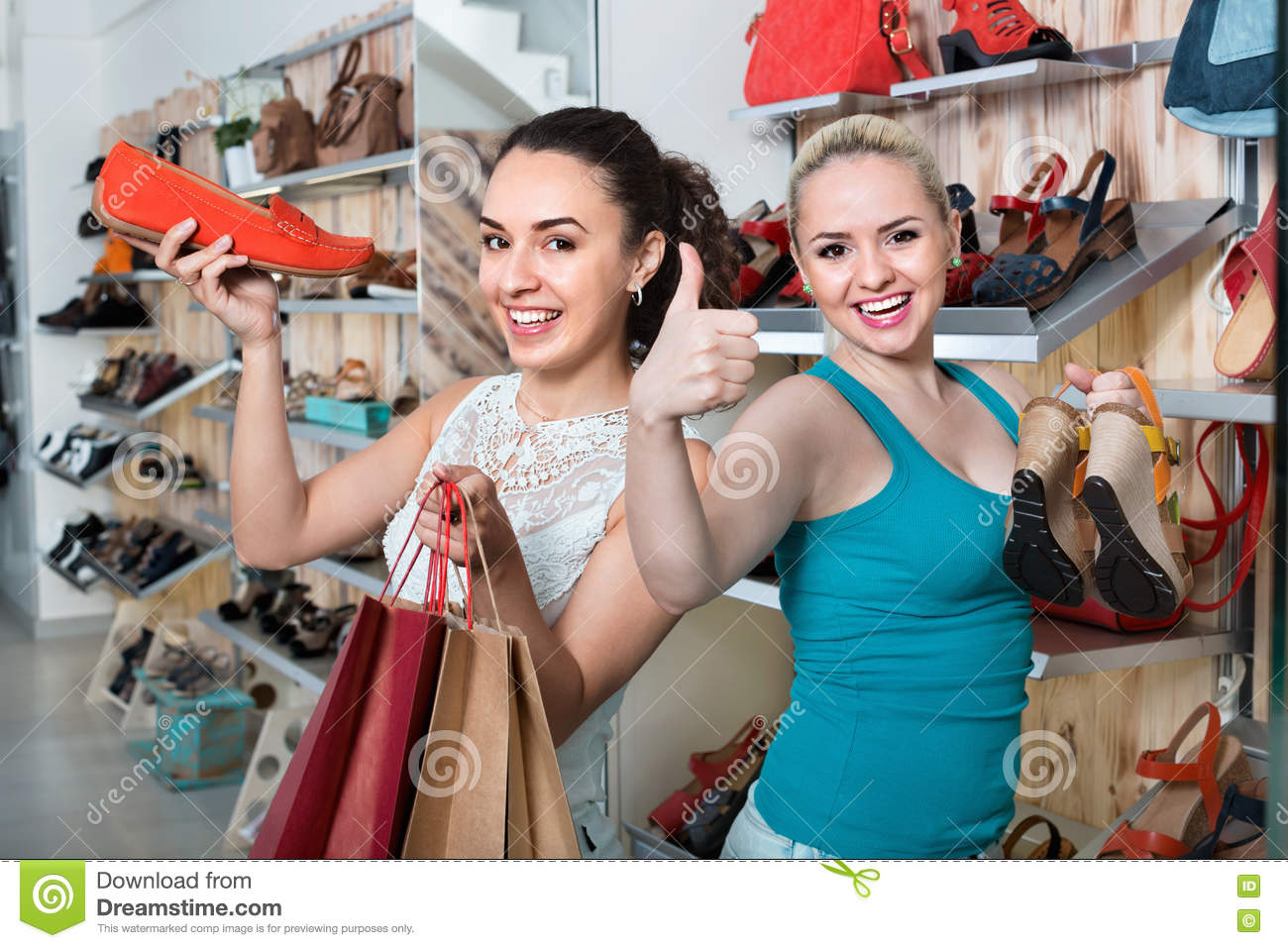Two Girls Holding A Paper Shopping Bags In The Boutique
