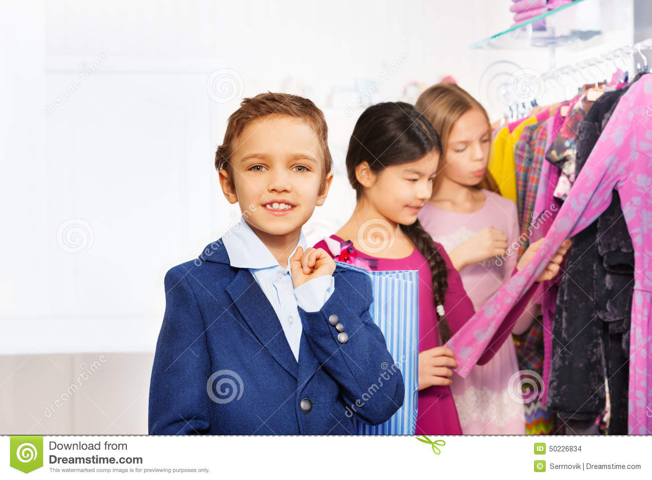 Download Two Girls And One Boy With Shopping Bag In Store Stock Photo