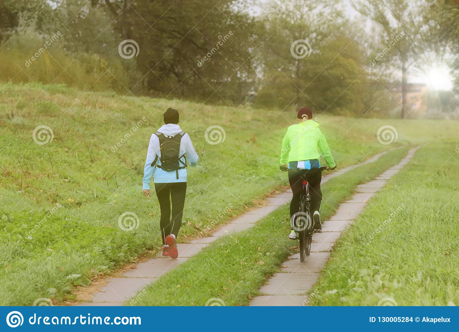 Two girls play sports in sunny morning`s weather. Cycling and walking under rain drops in sunny weather. Sport and healthy lifesty