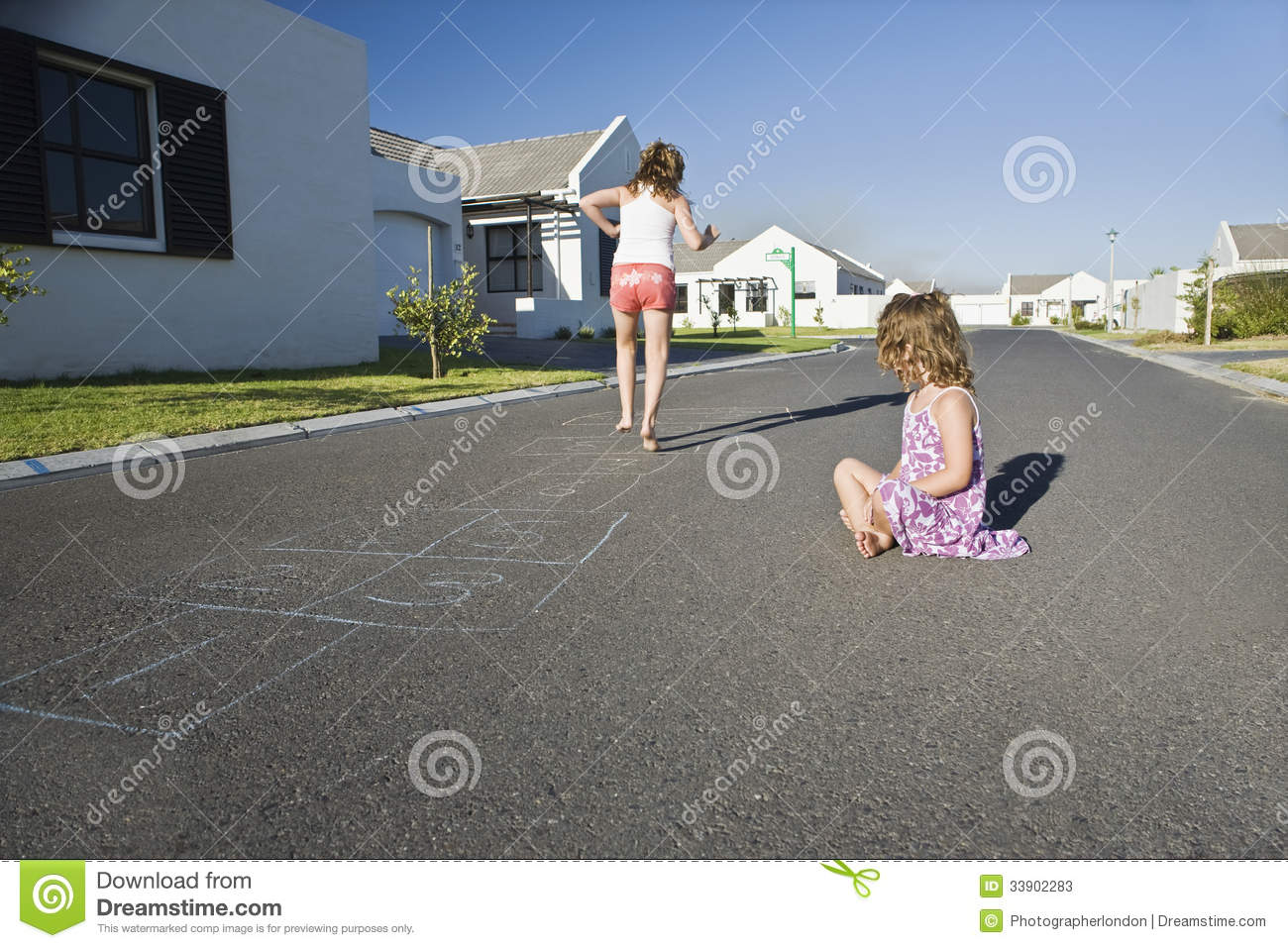 Two Girls Playing Hopscotch On Street Stock Photos Image 33902283