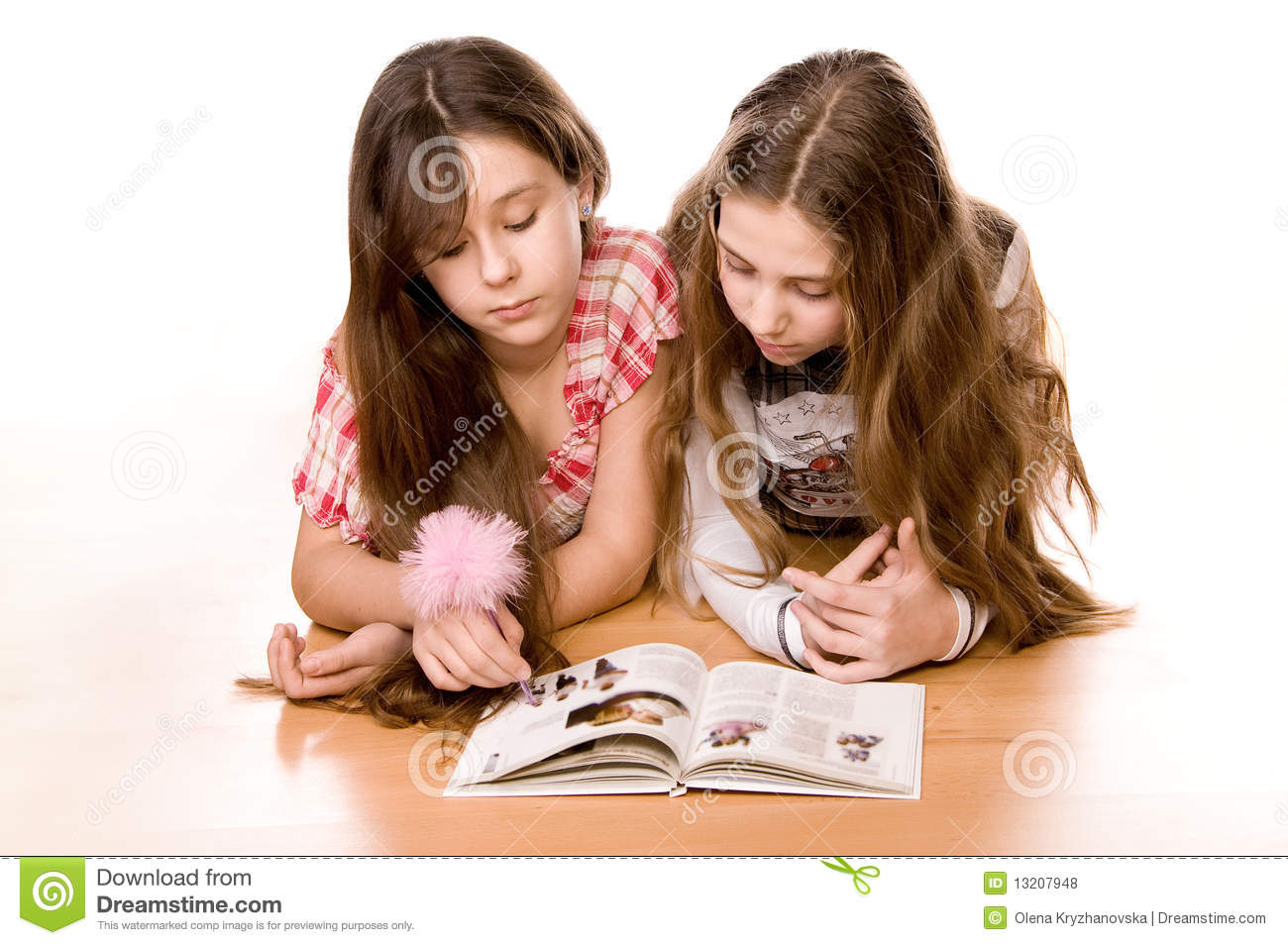 Two Girls Reading Book On The Floor On White Royalty Free