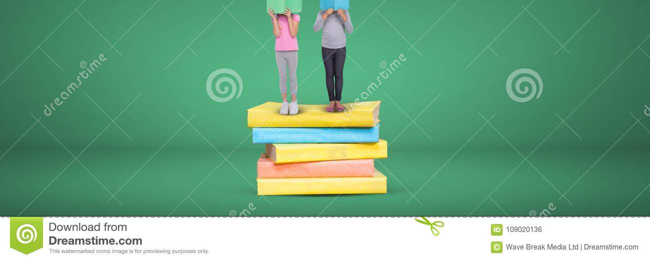Two girls reading and standing on a pile of books with green background
