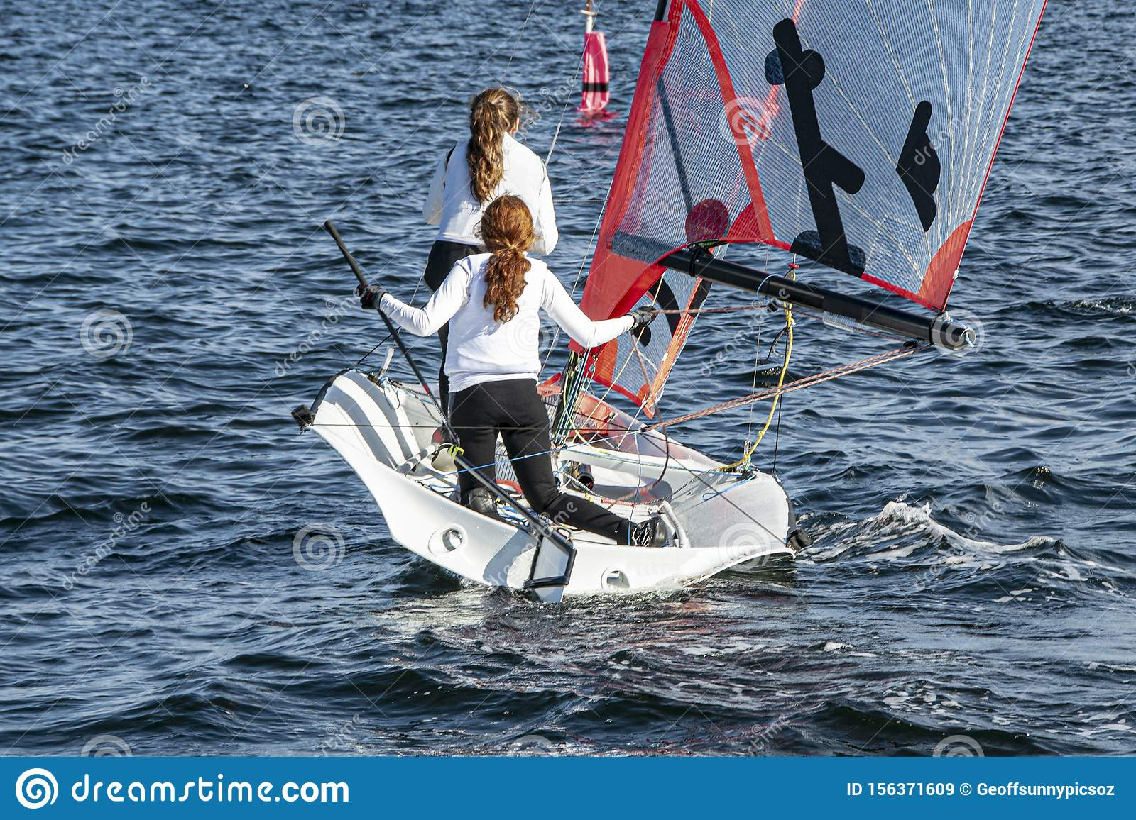 Two Girls Sailing Small Sailboat With Long Red Hair Viewed