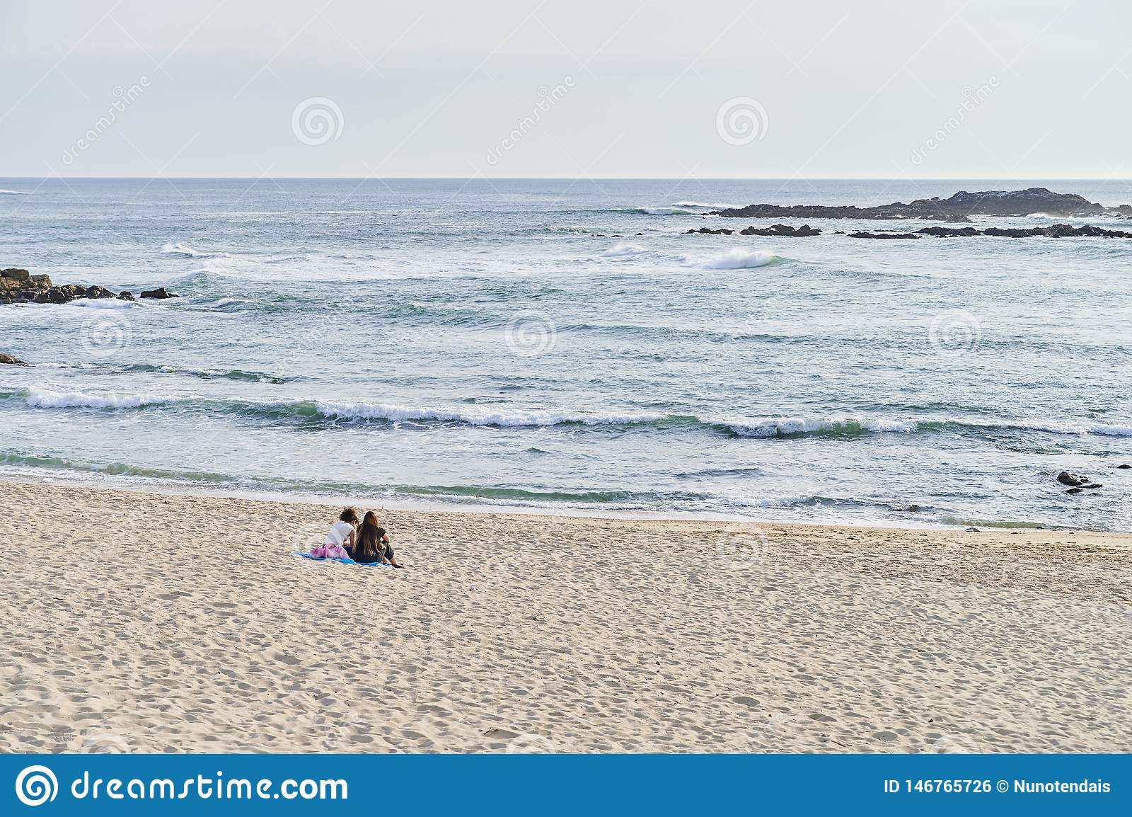 Teenagers seated talking alone on the beach