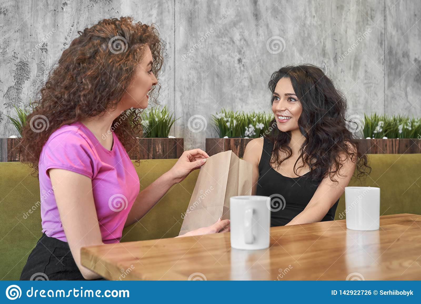 Two girls sitting in cafe, giving present.