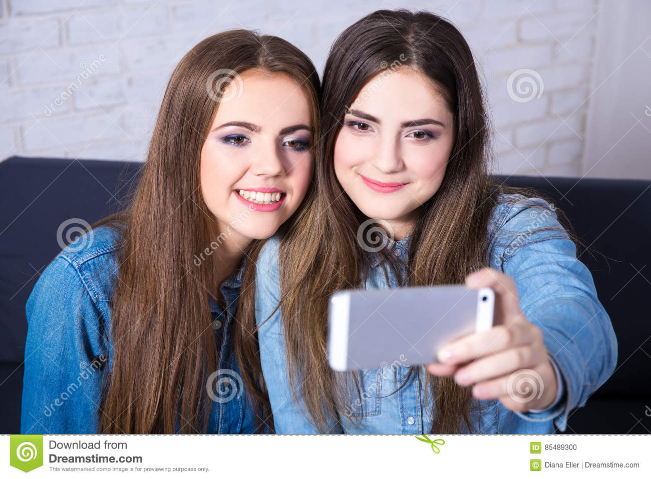 Two girls taking selfie photo with smart phone
