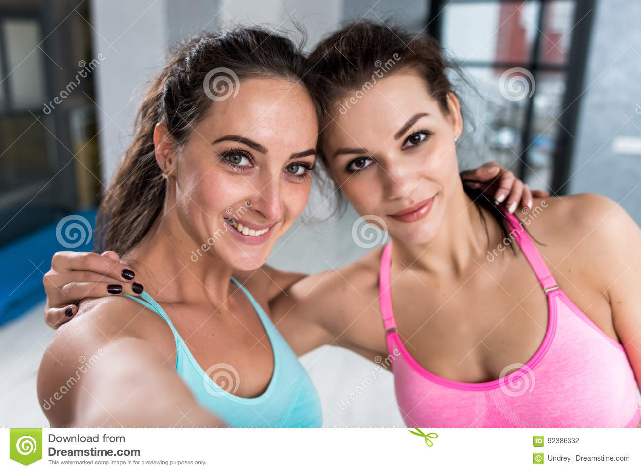 Two girls taking selfie wearing sports bra indoors. Close-up shot of female athletes smiling at camera hugging each