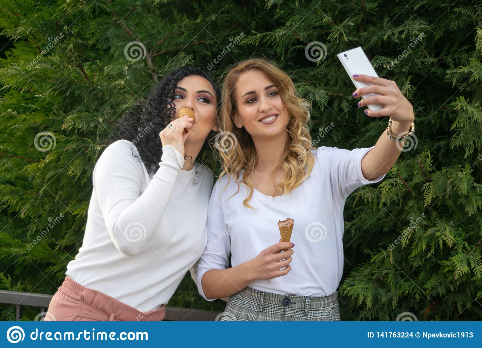 Two girls are taking selfies and eating ice cream