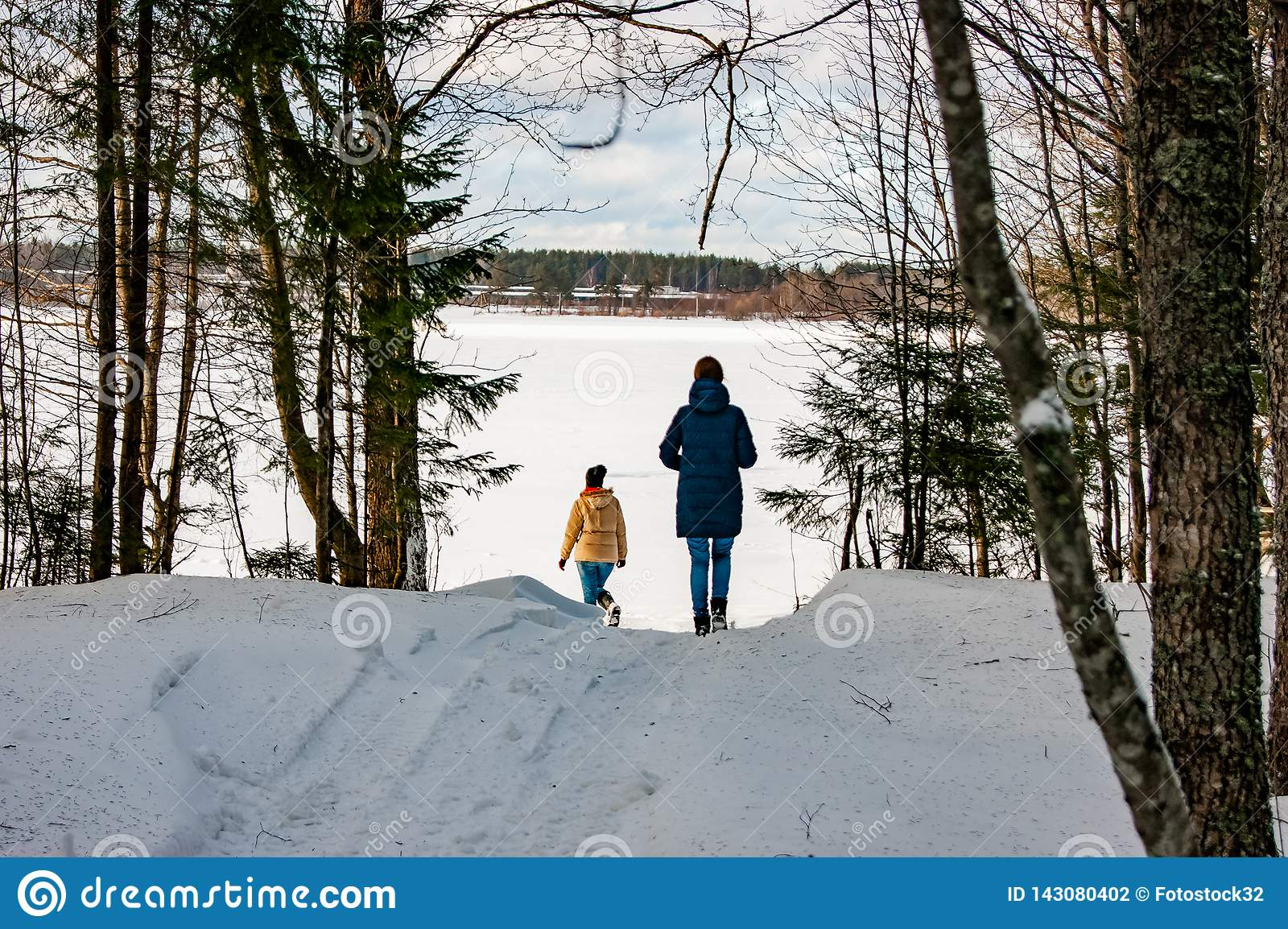 Two girls walk through the winter forest to the lake