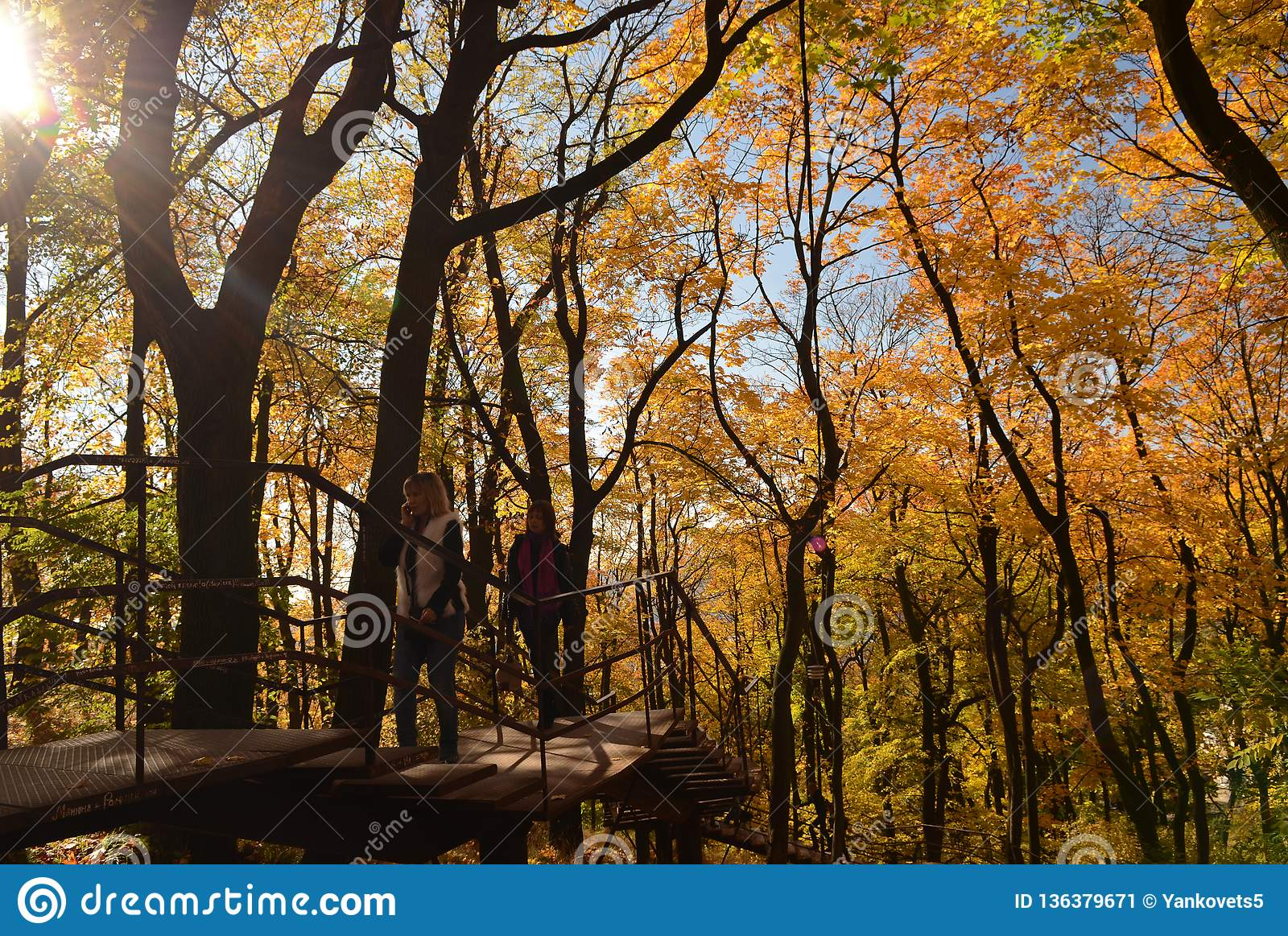 Two girls walk on a wooden staircase in the park under yellow trees