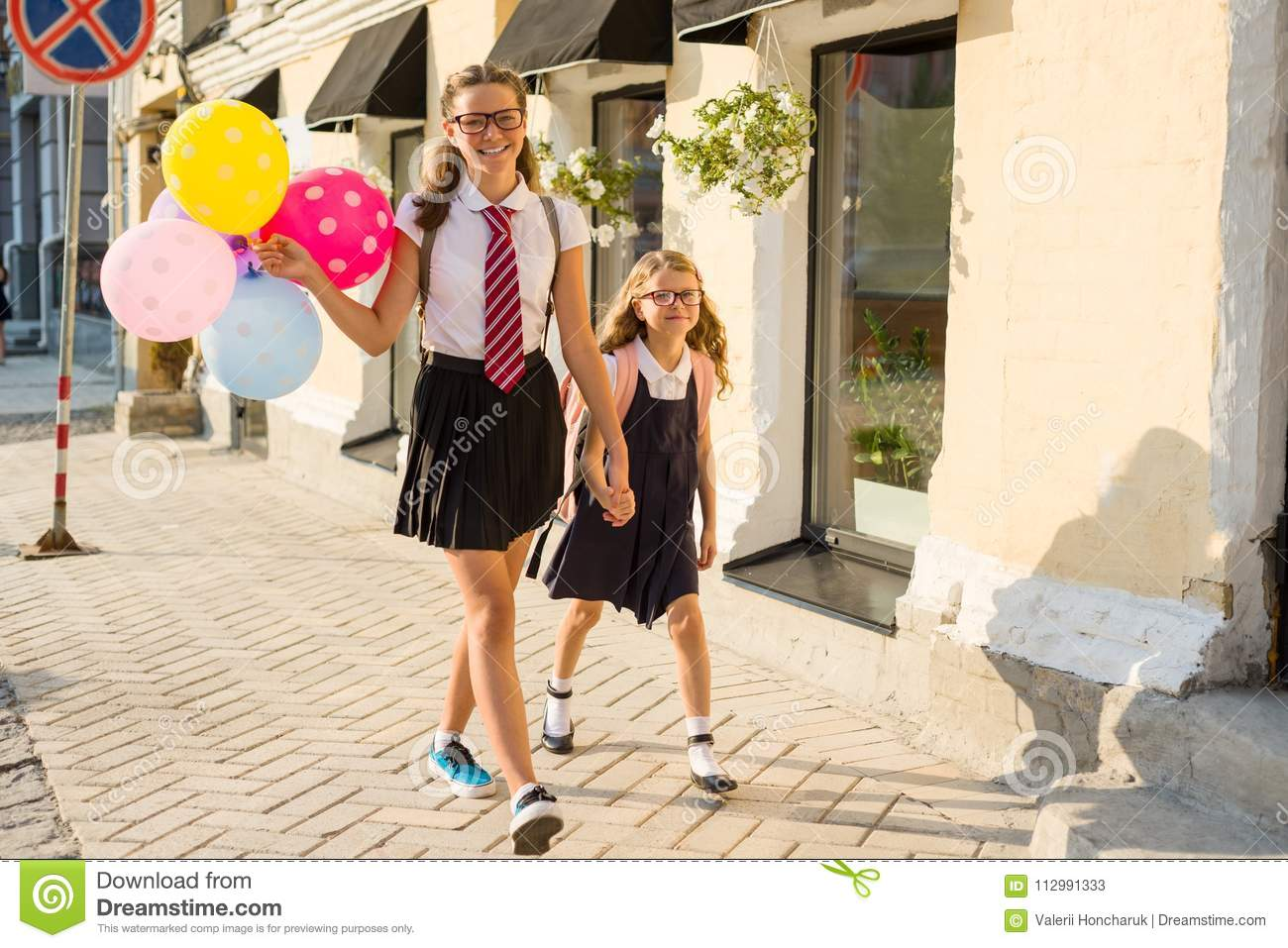 Two girls are walking along the street with colorful balloons. Children in school uniform, glasses, backpack