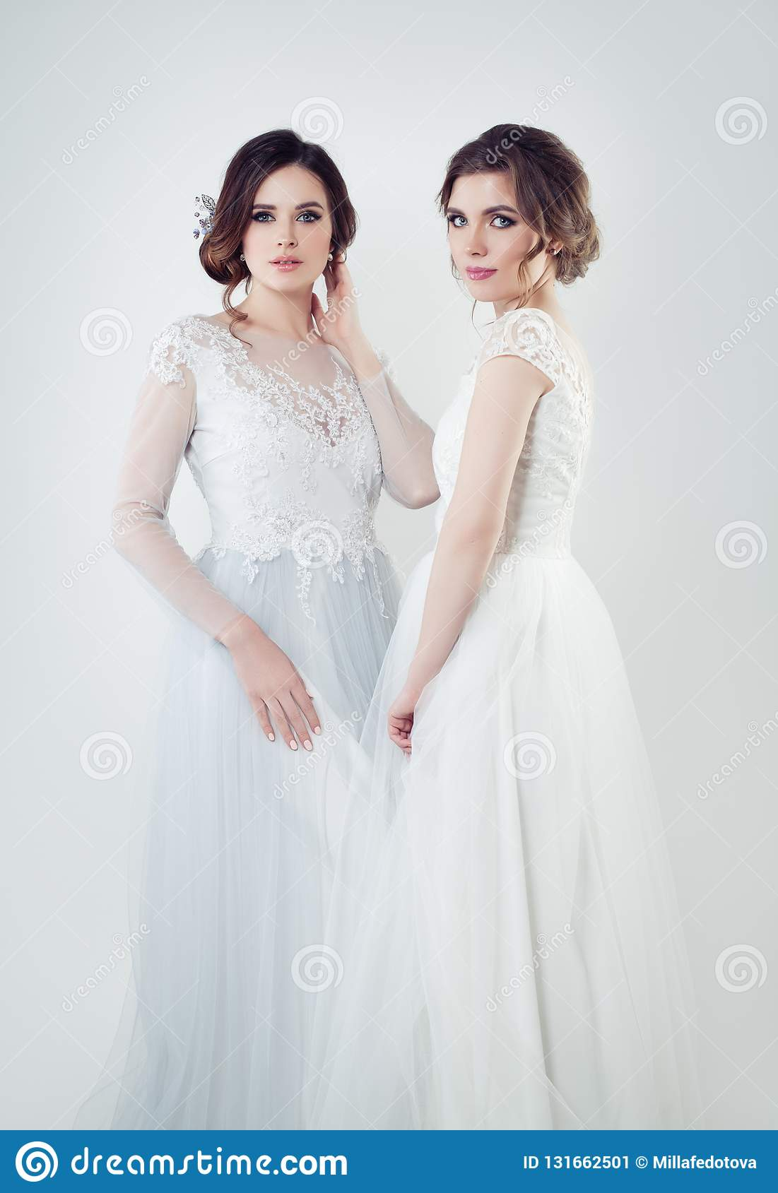 8f965c33f Two glamorous bride portrait. Perfect women in white wedding dress portrait.