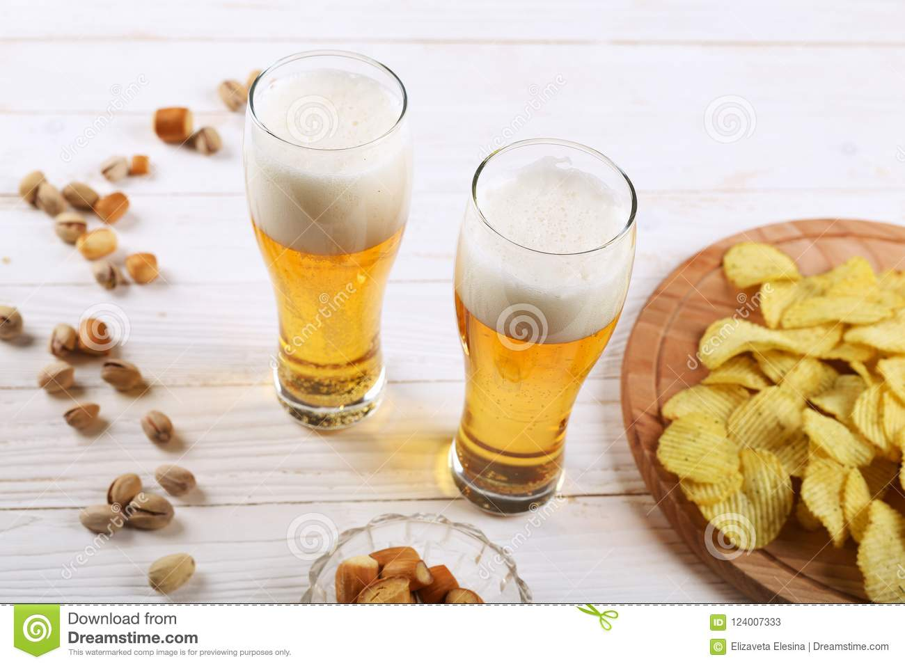 Two glass of beer and snacks on a white wooden table. Chips, pistachios, dry cheese.