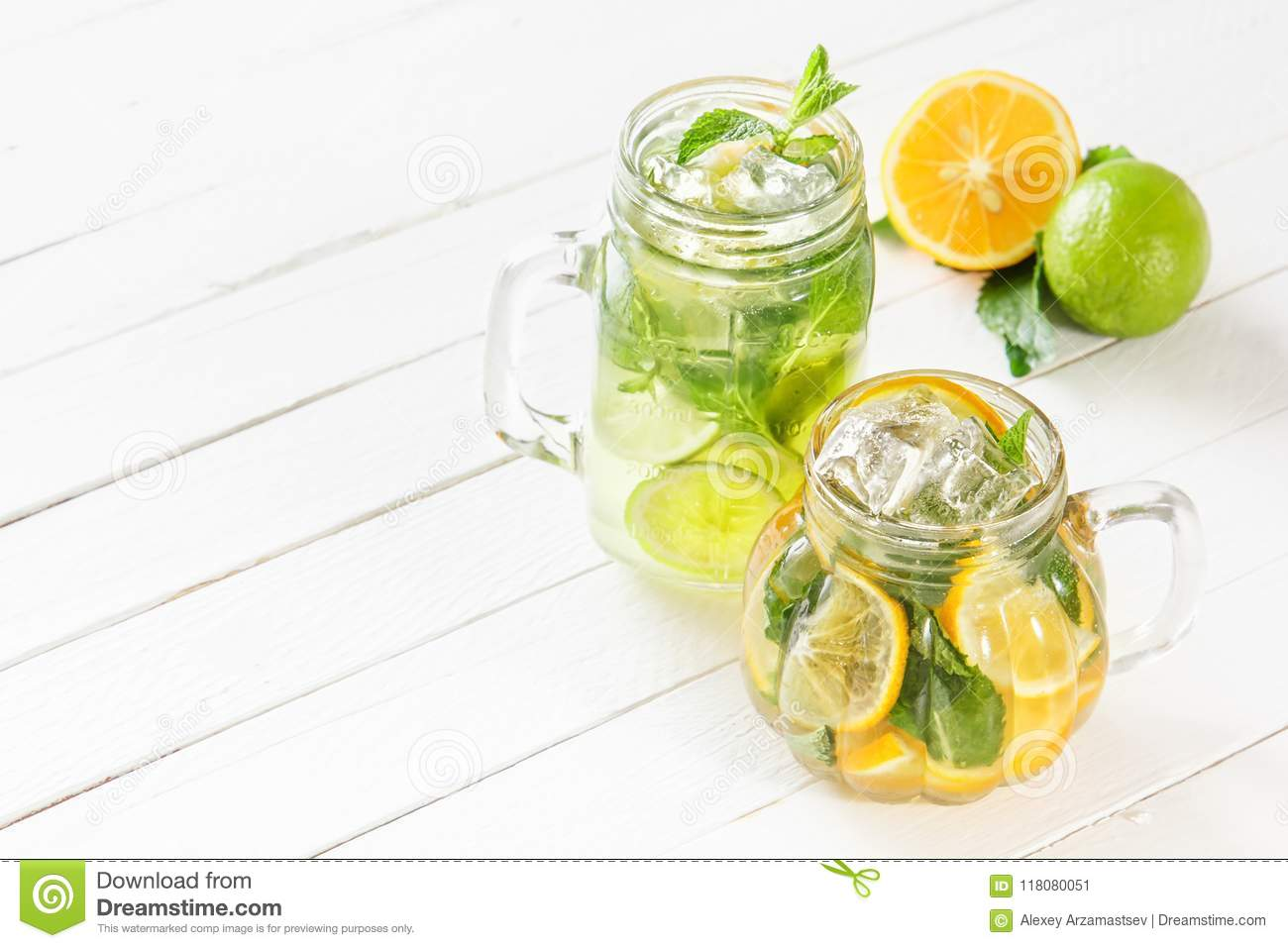 Two glass glasses with homemade lemonade from lime and lemon, sliced citrus on a white wooden rustic background