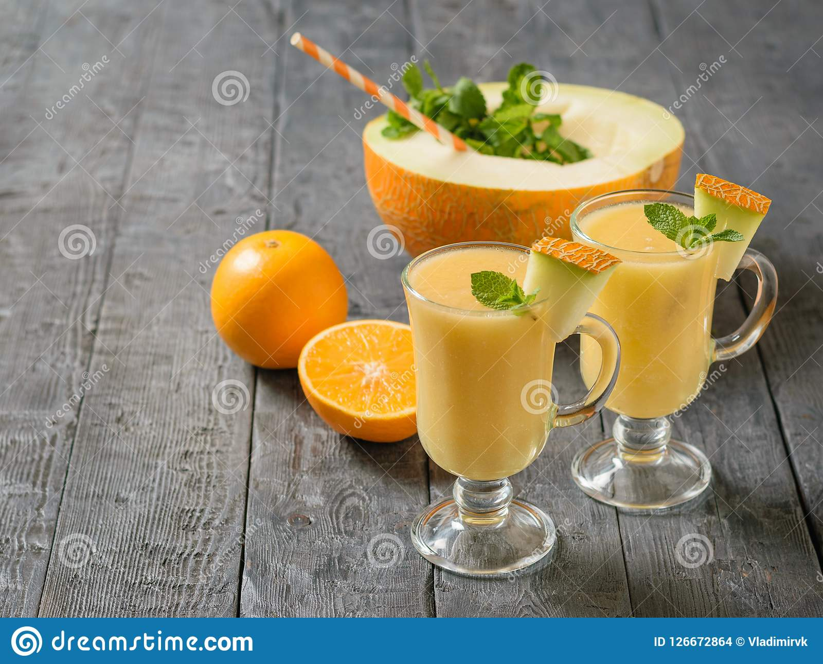 Download Two Glass Mugs With Melon Smoothie And A Half Melon With A Cocktail Tube On