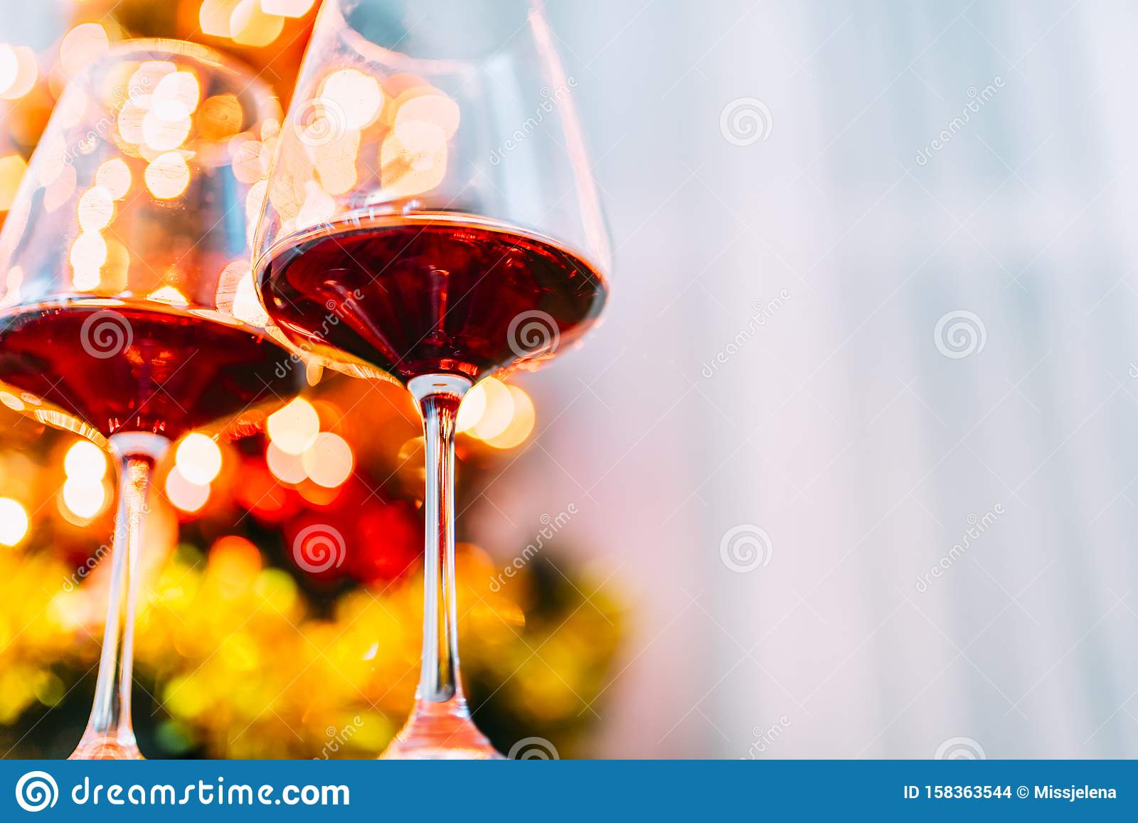Two glass of red wine in front of christmas tree lights bokeh. New year eve and xmas celebration party