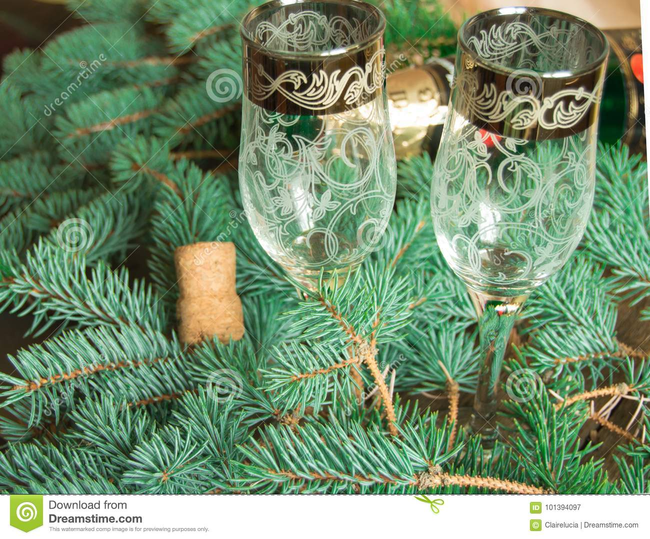 two glasses are on the background of fir branches with a bottle of champagne and cork, blurred background