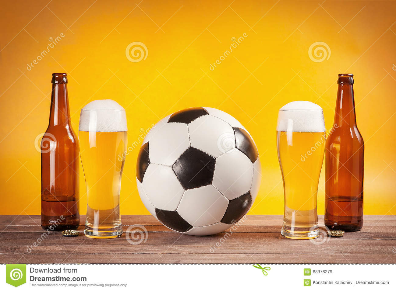 Two glasses of beer and bottles near soccer ball