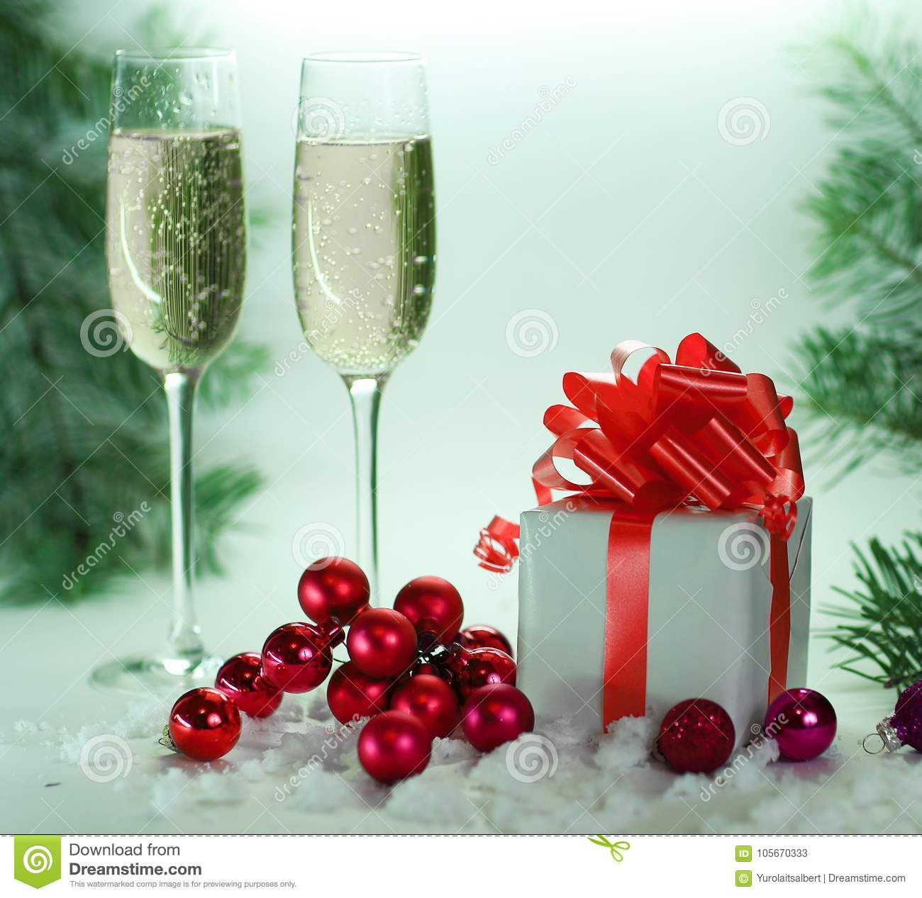 Two glasses with champagne, and boxes with gifts on Christmas ba