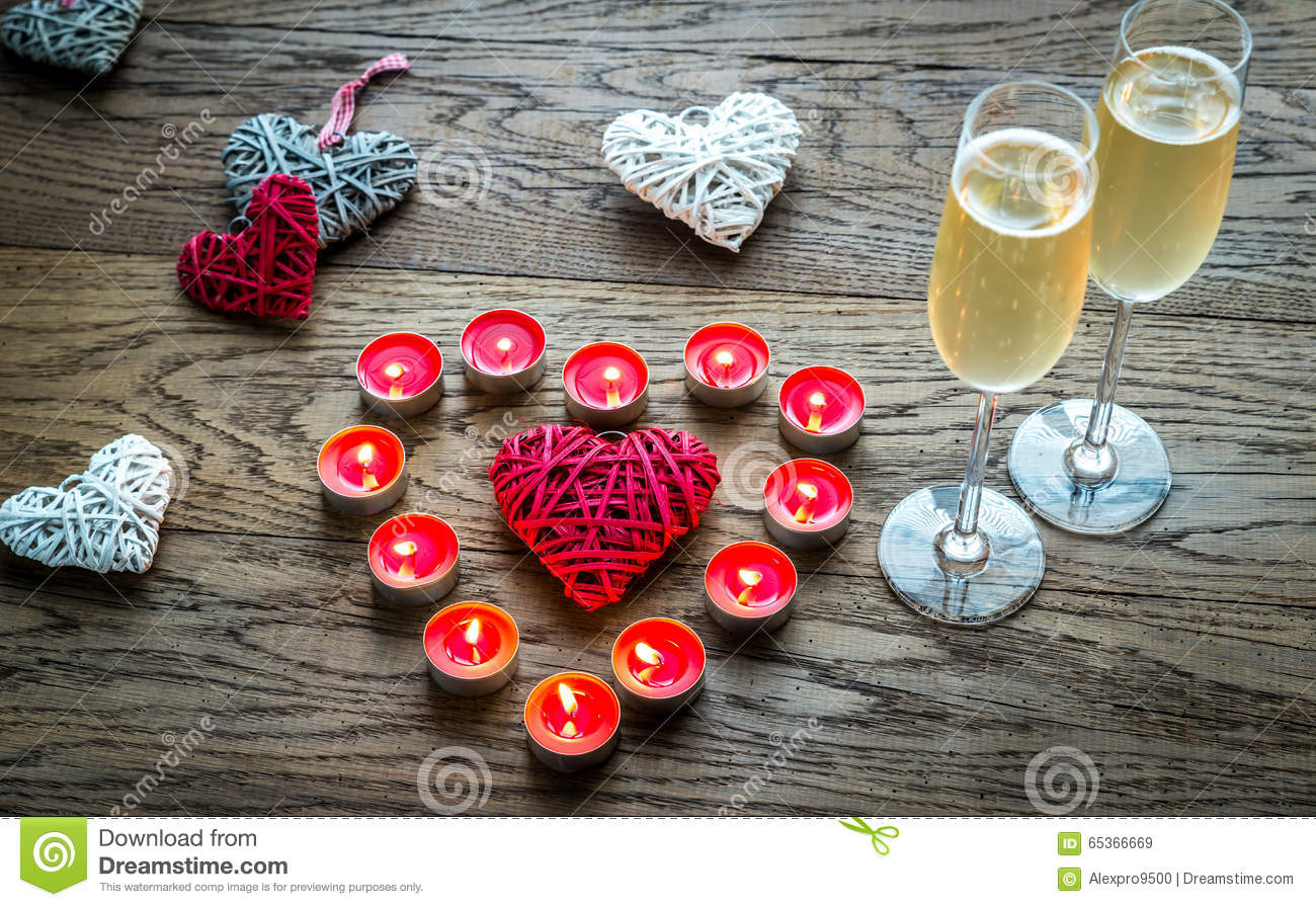 Two glasses of champagne with burning candles and cane hearts