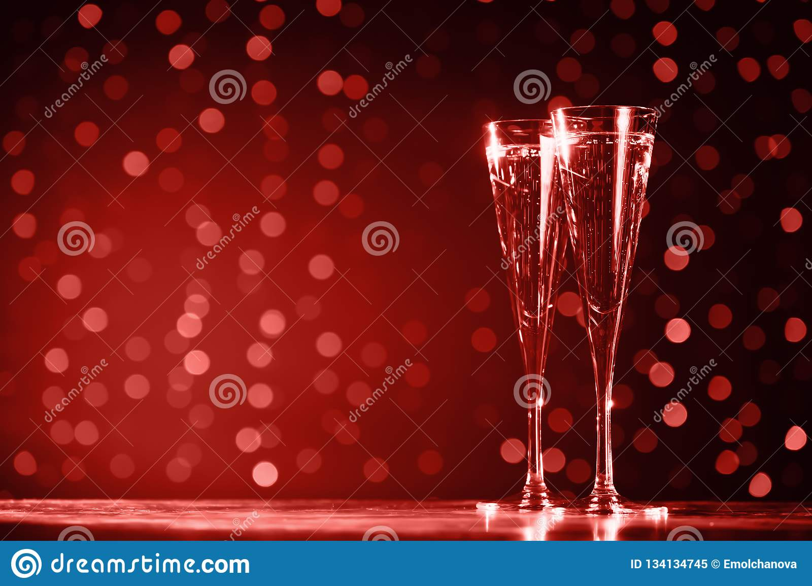 Two glasses of champagne on dark bokeh background. Ultra violet tone, color of the year 2018 . Living coral theme - color of the