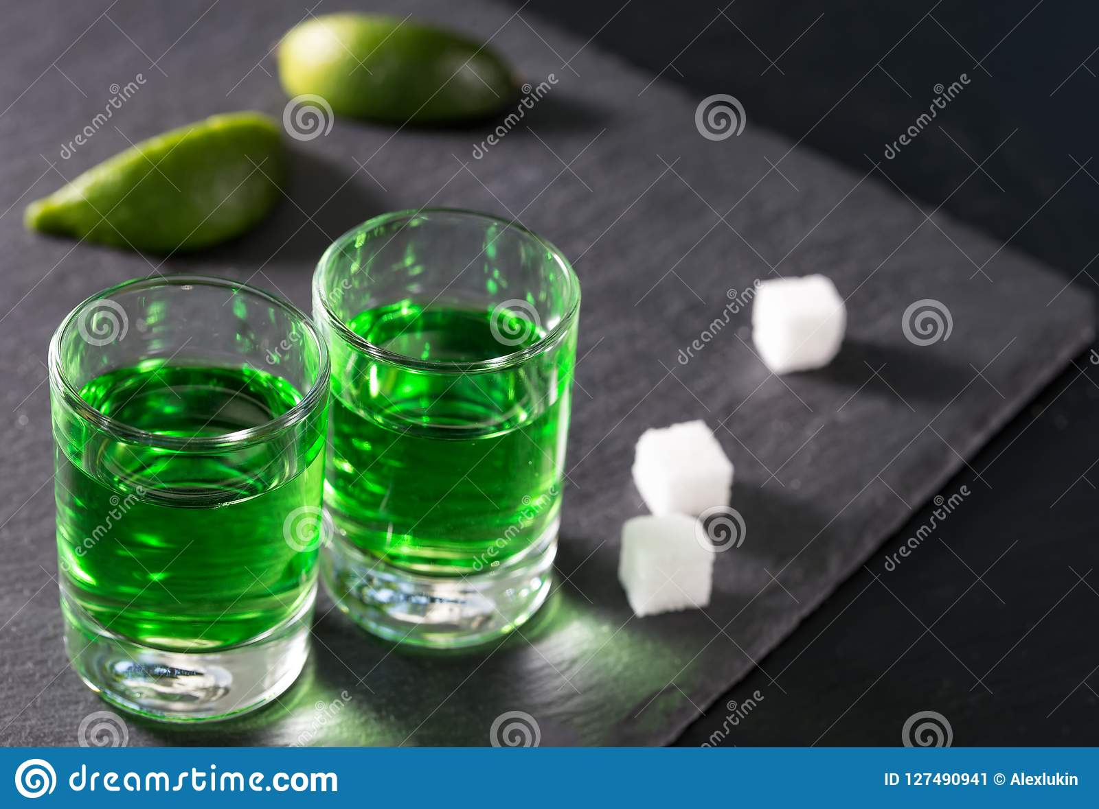 Two glasses with green absinthe lime and sugar