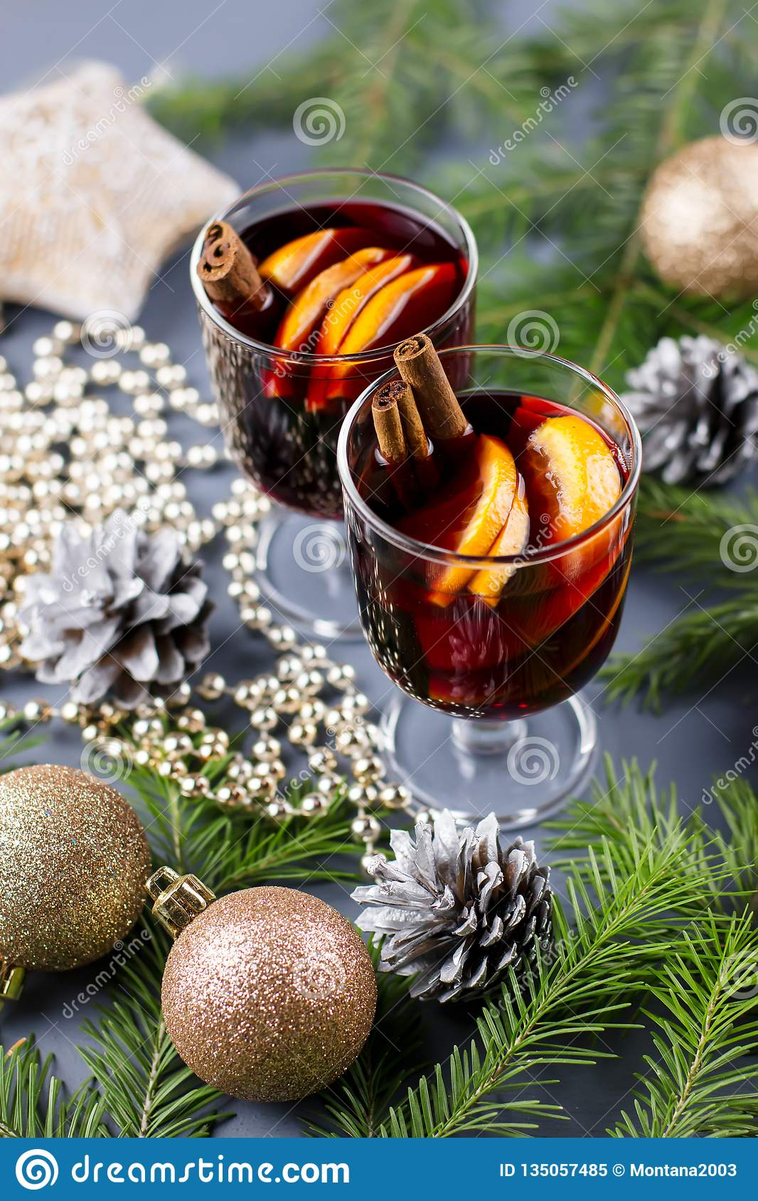 Two glasses of hot mulled wine with spices and sliced orange. Christmas drink with candle and decorations. Top view