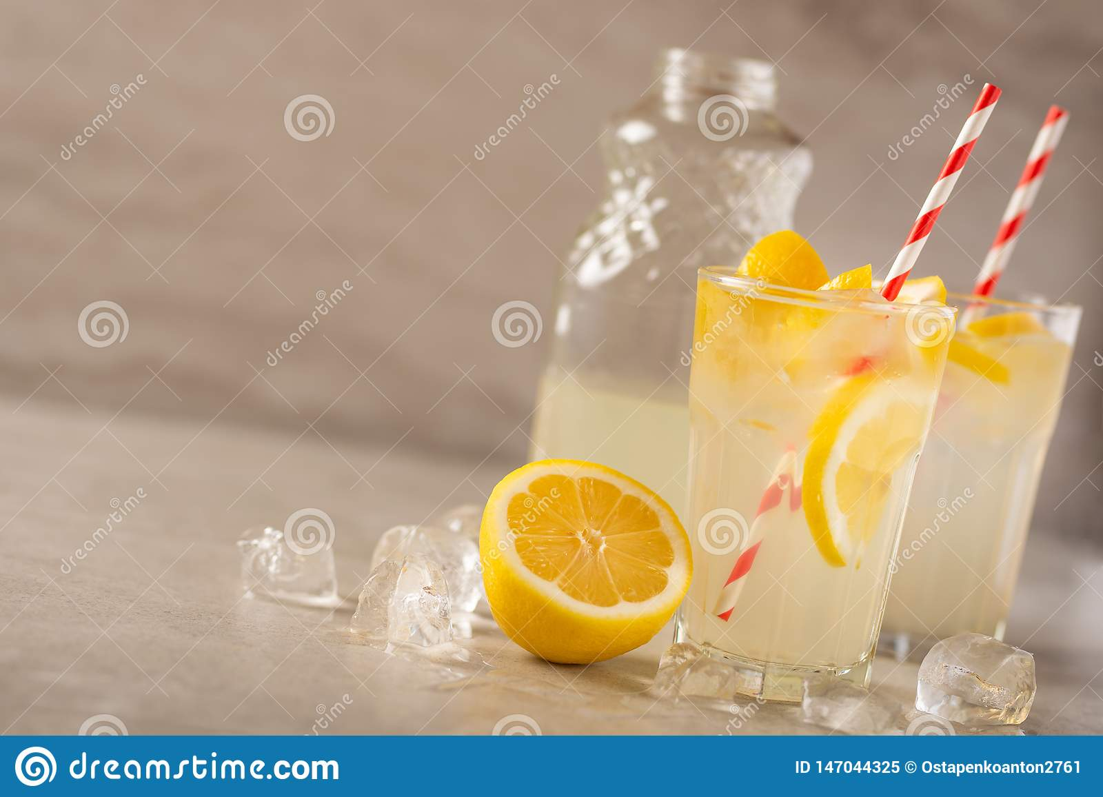 Two glasses of lemonade with lemons and lime and straw, a bottle with a cool drink and summer mood, with ice, freshness in hot