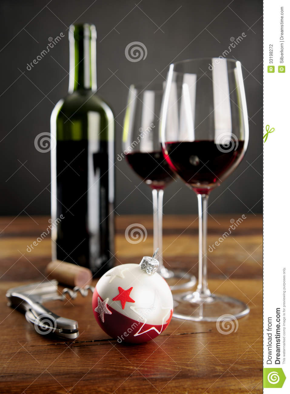 Two glasses of red wine and christmas baubel