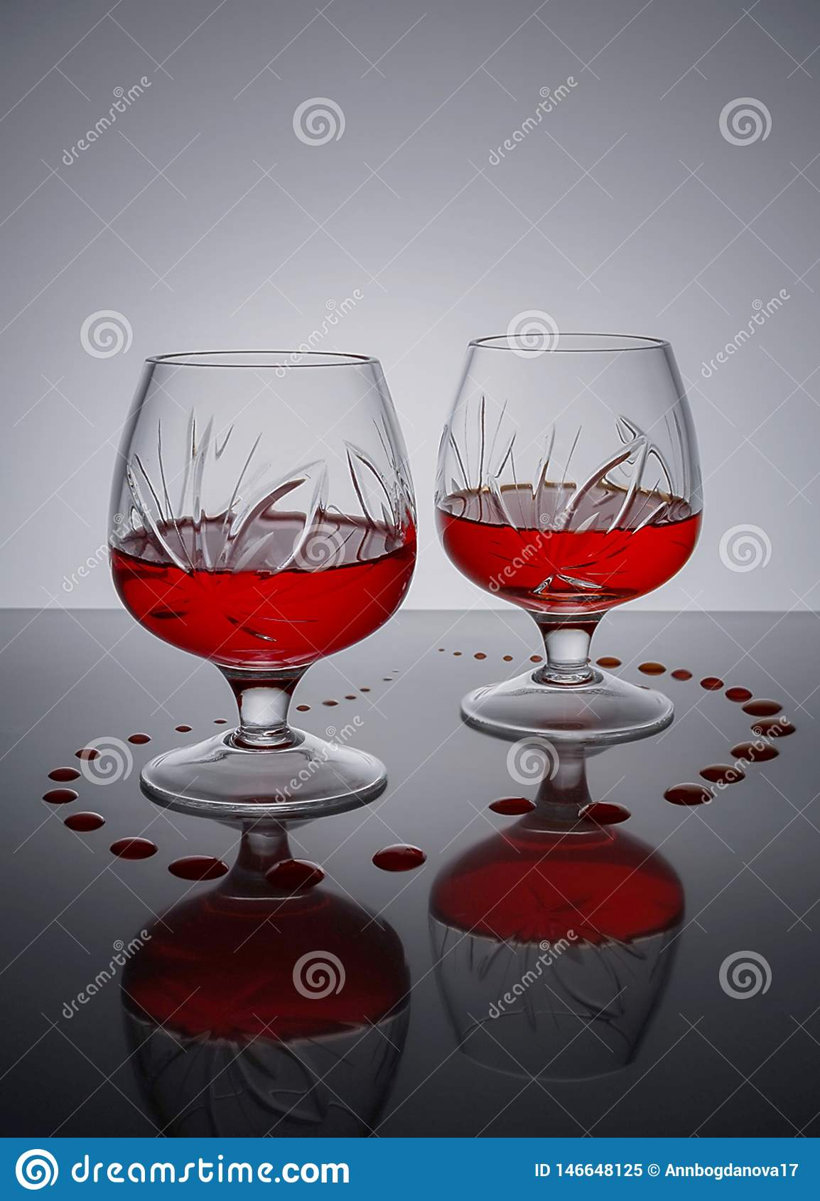 Two glasses of red wine on a plastic surface