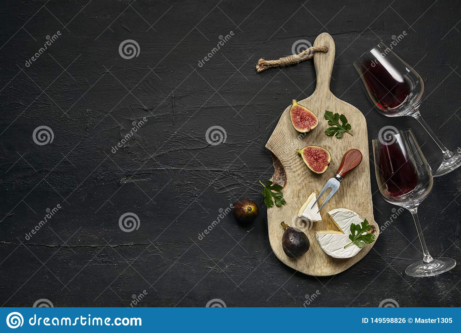 Two glasses of red wine and a tasty cheese plate on a wooden kitchen plate.