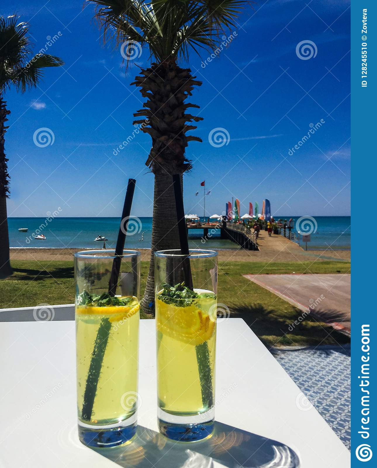 Two glasses on table, sea, palm