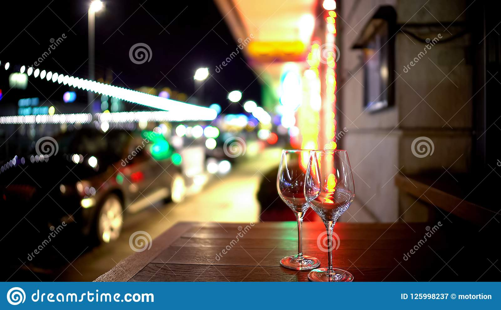 Two glasses on table in street cafe, romantic evening, spontaneous acquaintance