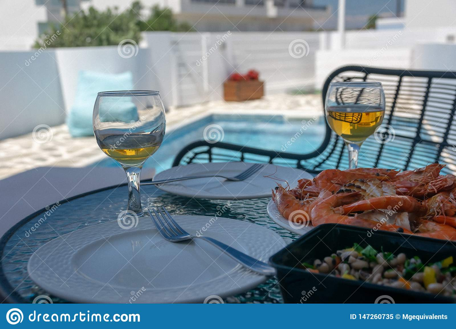 Two glasses of white wine and shrimps on the table by the pool