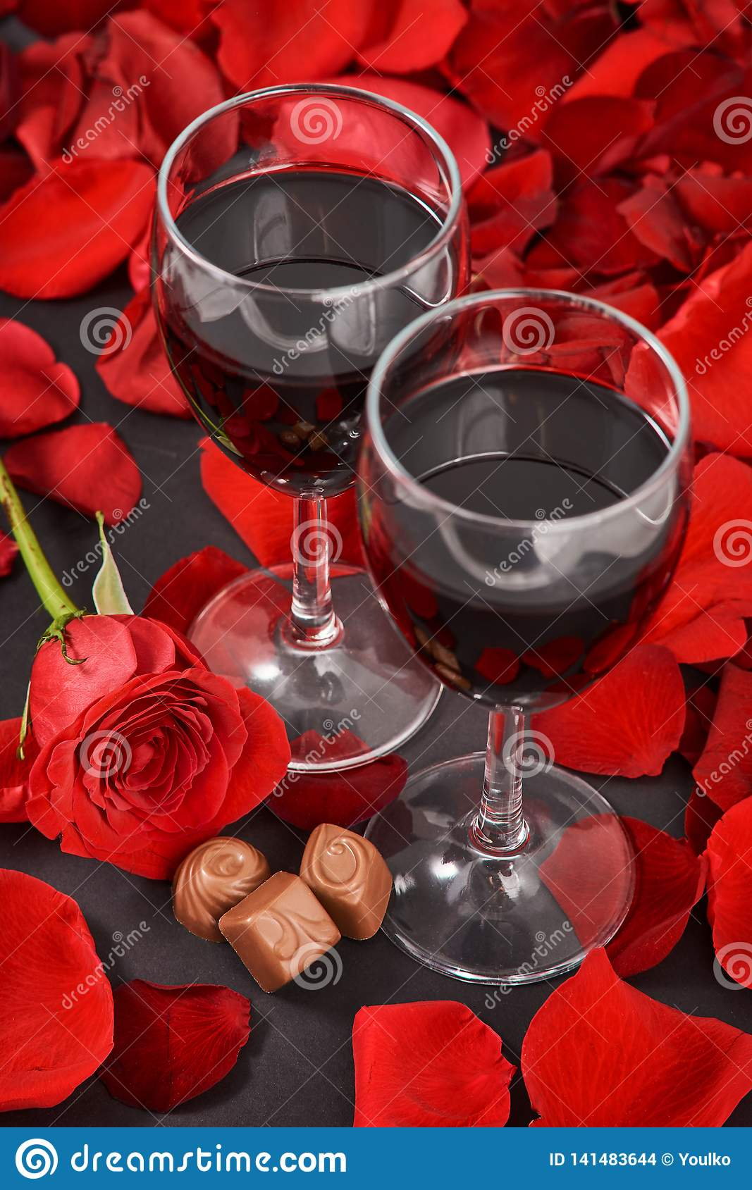 two glasses of wine, rose, petals and chocolates on a black background