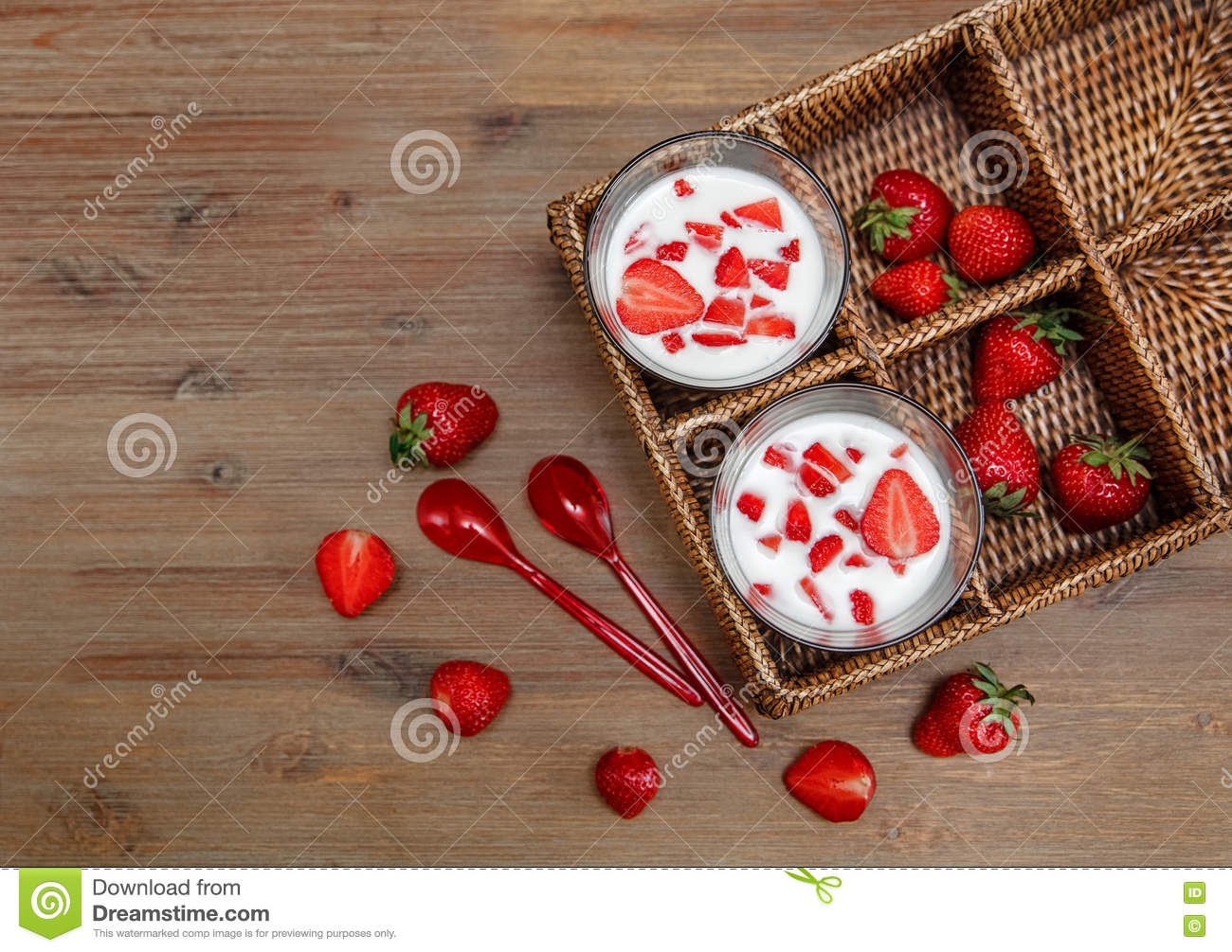 Two Glasses of Yogurt,Red Fresh Strawberries in the Rattan Box with Plastic Spoons on the Wooden Table.Breakfast Organic Healthy
