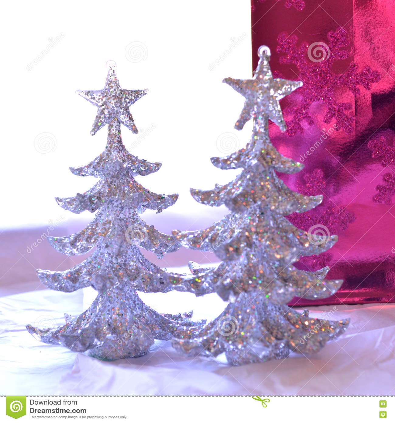 Two glittery Christmas trees in front of glittery bright pink gi